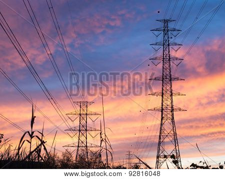 Parallel high voltage electricity pylon on the orange sky in the evening.