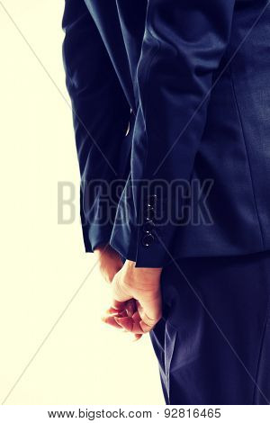Close up on businesswoman clenching hands behind her back.