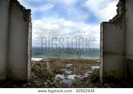 Destroyed House Stands On The Cliff By The Sea.