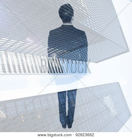 Asian businessman against low angle view of skyscrapers