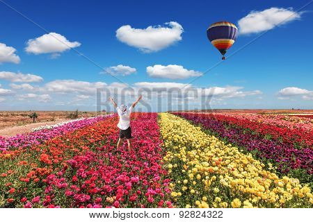 Enthusiastic tourists threw up his hands. Big balloon flies over field of flowering.