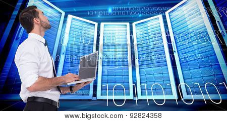 Sophisticated businessman standing using a laptop against composite image of server room