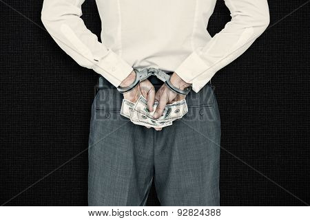 Businessman in handcuffs holding bribe against black background
