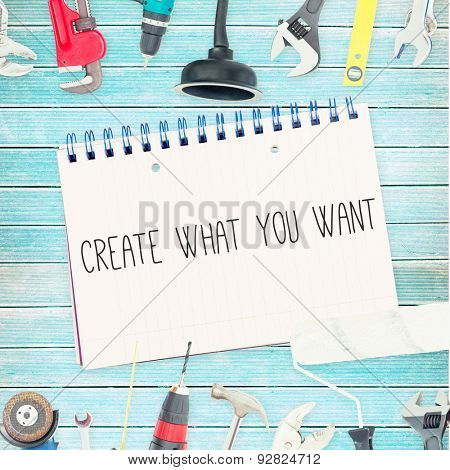 The word create what you want against tools and notepad on wooden background