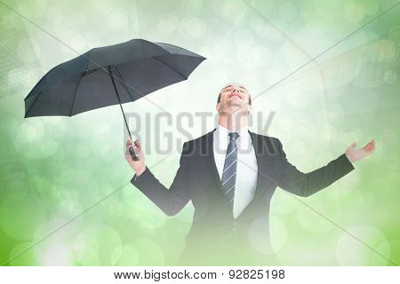 Businessman sheltering under black umbrella testing against green abstract light spot design