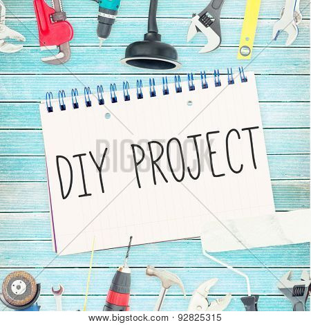 The word diy project against tools and notepad on wooden background