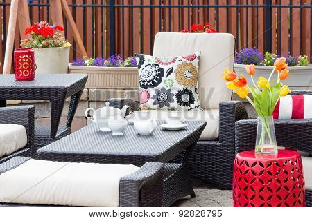 Tea Served On An Outdoor Patio Between Flowers