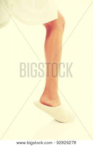 Female bare foot in white slippers.