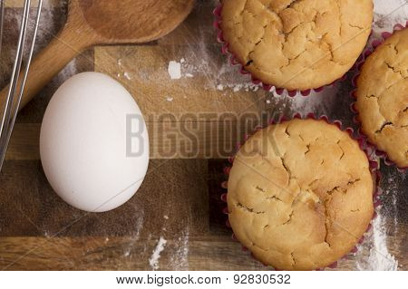 Muffins In Cupcake Cases On A Flour Covered Cutting Board