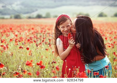 Mother and her 7 years old preteen child playing in spring poppy field in soft sunlight. Mom kissing daughter.