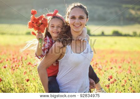 Mom and her 6 years old child playing in spring flower field