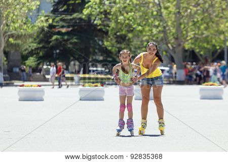 Young mom with her 6 years old child rollerskating in the city street