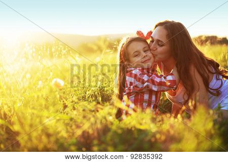 Mom and her 6 years old child playing in spring field. Mother kissing daughter.