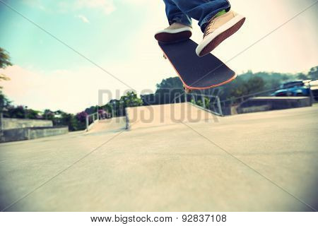 skateboarder legs doing a track ollie at skatepark