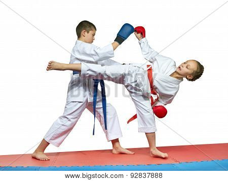 Boy and girl in karategi are training paired exercises karate