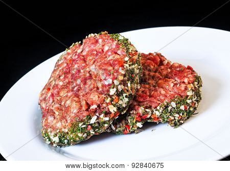 Closeup Of Raw Red Hamburgers On White Plate Isolated On Black