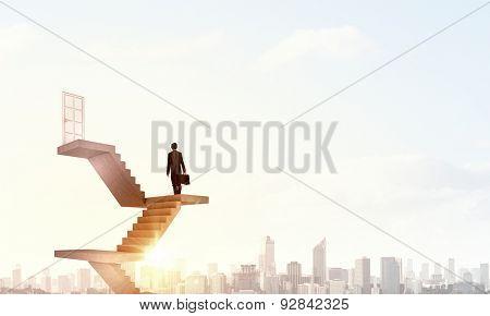 Businessman walking up staircase to door in sky