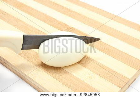 Closeup Of Knife Cutting Egg On Wooden Background