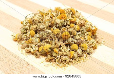 Heap Of Dried Chamomile On Wooden Background