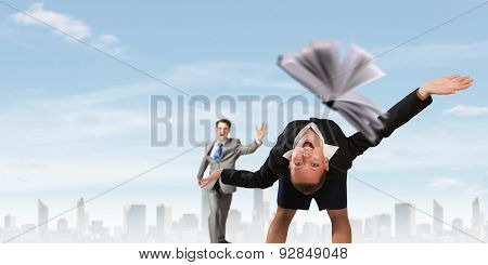 Young businesswoman trying to evade from thrown book