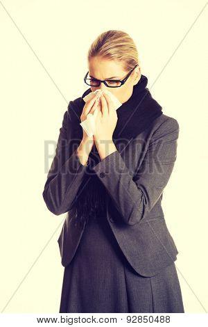 Beautiful woman sneezing because of flu