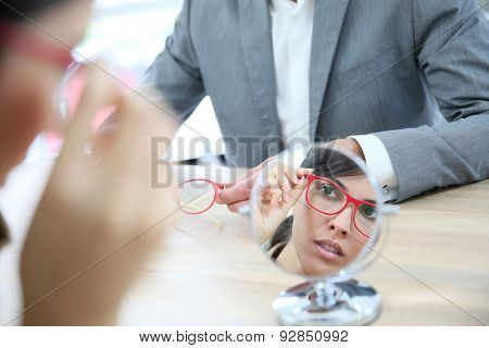 Woman in optical store choosing eyeglasses