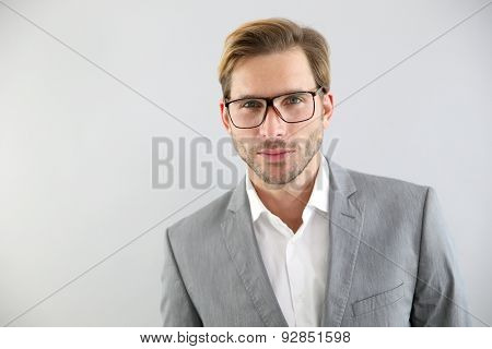 Businessman with eyeglasses standing on grey background, isolated