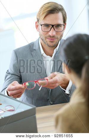 Optician presenting new eyeglasses to customer