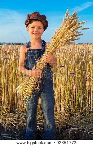 Happy farmer's boy with sheaf
