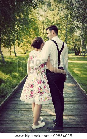 Young couple embrace in summer park standing on straight wooden path. Woman in dress and man wearing shirt with braces. View from the back. Dating, future plans concepts