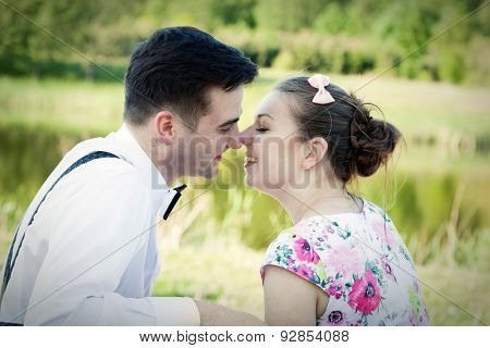 Young couple in love looking at each other in the eyes in summer park. Woman in dress and man wearing shirt with suspenders and bow tie.