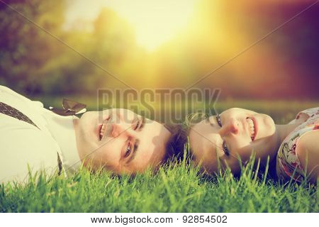 Happy couple in love smiling while lying on summer grass. Dating, romantic mood, sun light.