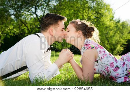 Romantic couple in love kissing while lying on grass in spring park. Vintage date, woman in dress and man wearing suspenders with bow tie.