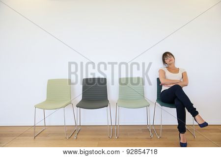 Young woman in waiting room falling asleep