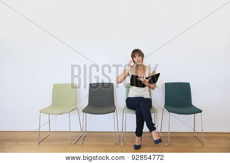 Businesswoman in waiting room with agenda and phone