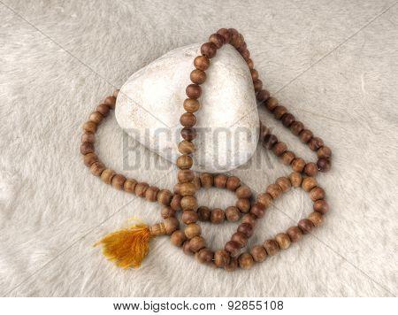 Tibetan mala on a white stone