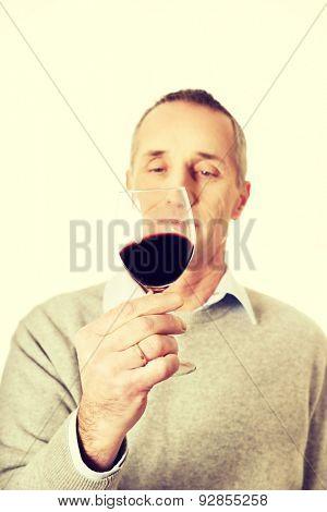 Mature man tasting red wine.