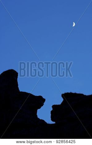 Moon and rocky pinnacles with clear sky.