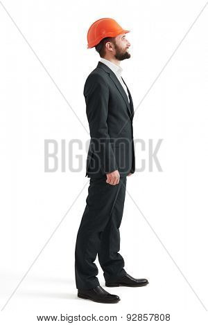 sideview of smiley man in formal wear and orange hard hat. isolated on white background