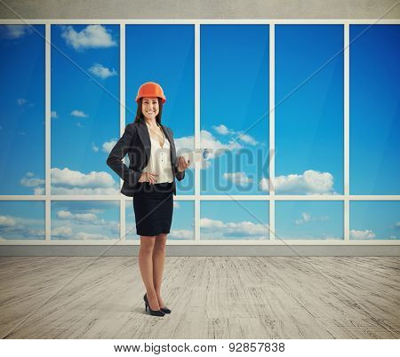 smiley woman architect in orange hardhat holding plan and looking at camera in room with big windows