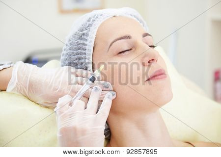 beautiful woman getting an injection in her face at beauty salon
