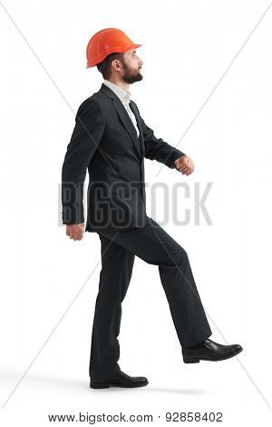 businessman in formal wear and orange hardhat doing one step and looking up. isolated on white background