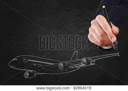 Close up of hand drawing airplane on black background