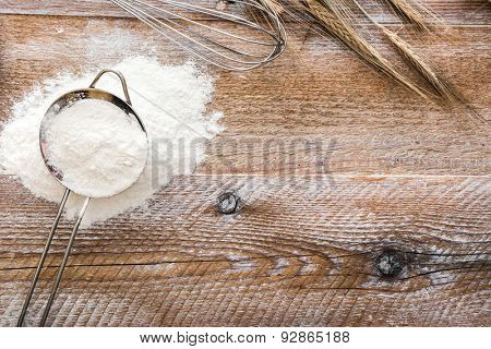 Sieve with flour on wooden board