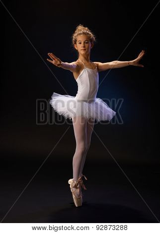 Pretty young ballet dancer standing on her toes, practicing over black background.