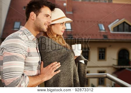Young loving couple embracing in balcony. Side view.