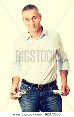 Confused man showing his empty pockets.