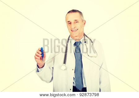 Experienced mature male doctor holding a thermometer.