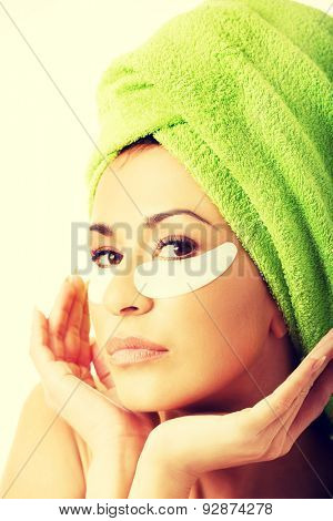 Spa serene woman with gel eye mask and hands on chin