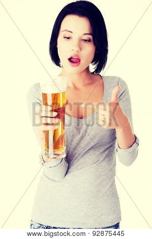Young surprised woman holding a glass of beer.